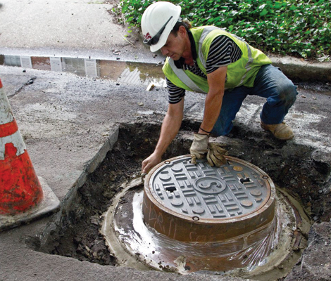 Man installing manhole in street