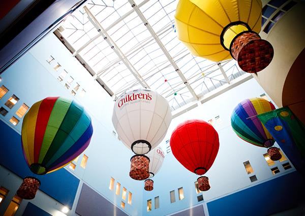 Looking up at small hot air balloons in a building for Children's Hospital