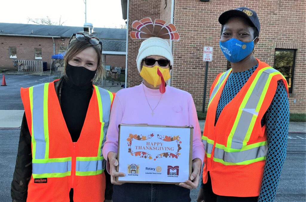 3 women in masks and safety vests in a parking lot