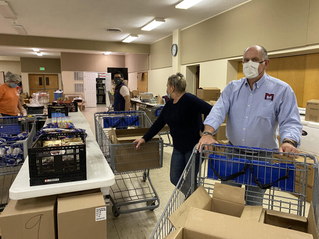 Man moving food in a cart at a food pantry